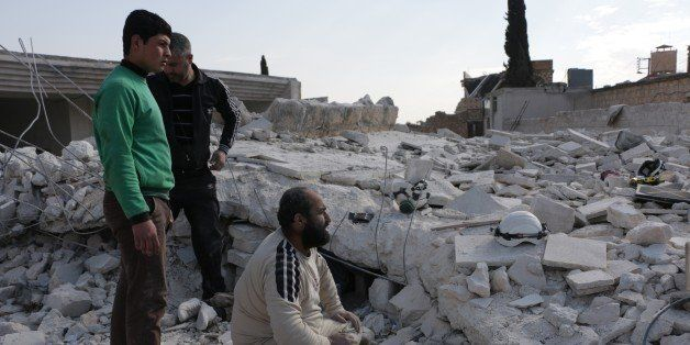 ALEPPO, SYRIA - FEBRUARY 2: Civil defense team members try to clear the debris of a building to rescue the people buried unde