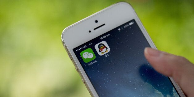 The icons for Tencent Holdings Ltd.'s messaging applications WeChat, left, and QQ are displayed on an Apple Inc. iPhone 5s sm