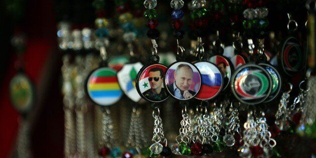 Key-rings bearing portraits of Syrian President Bashar al-Assad (L) and his Russian counterpart Vladimir Putin (C) are displa