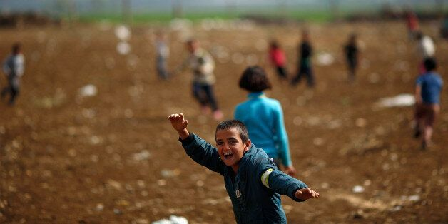 A Syrian refugee boys play at a refugee camp in the town of Hosh Hareem, in the Bekaa valley, east Lebanon, Wednesday, Oct. 2