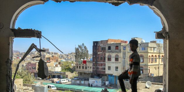 TOPSHOT - A Yemeni boy checks the damage following a mortar shell attack on the country's flashpoint southern city of Taez on