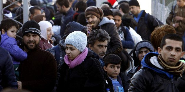 Refugees gather upon their arrival at the transit center for refugees near northern Macedonian village of Tabanovce, before c