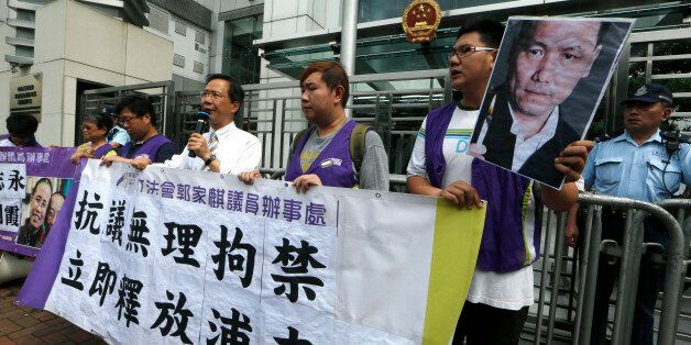 Anti-Beijing protesters, holding pictures of human rights lawyer Pu Zhiqiang, protest outside the Chinese liaison office to d