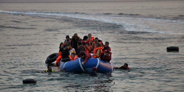 Refugees and migrants massed onto an inflatable boat reach Mytilene, northern island of Lesbos, after crossing the Aegean sea