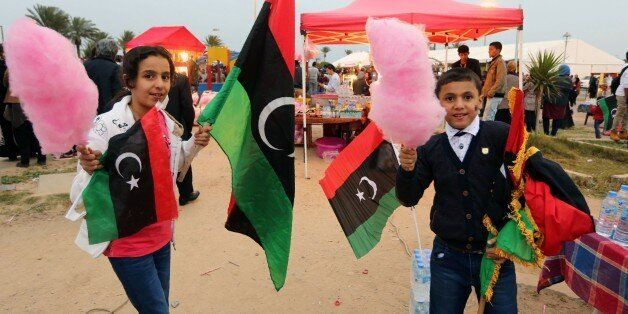 Libyans wave national flags as they gather at Martyrs' Square in the capital Tripoli on February 16, 2016 to attend the celeb