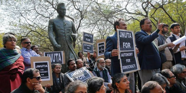 Teachers gather near a statue of Jawaharlal Nehru during a protest at the Jawaharlal Nehru University against the arrest of a