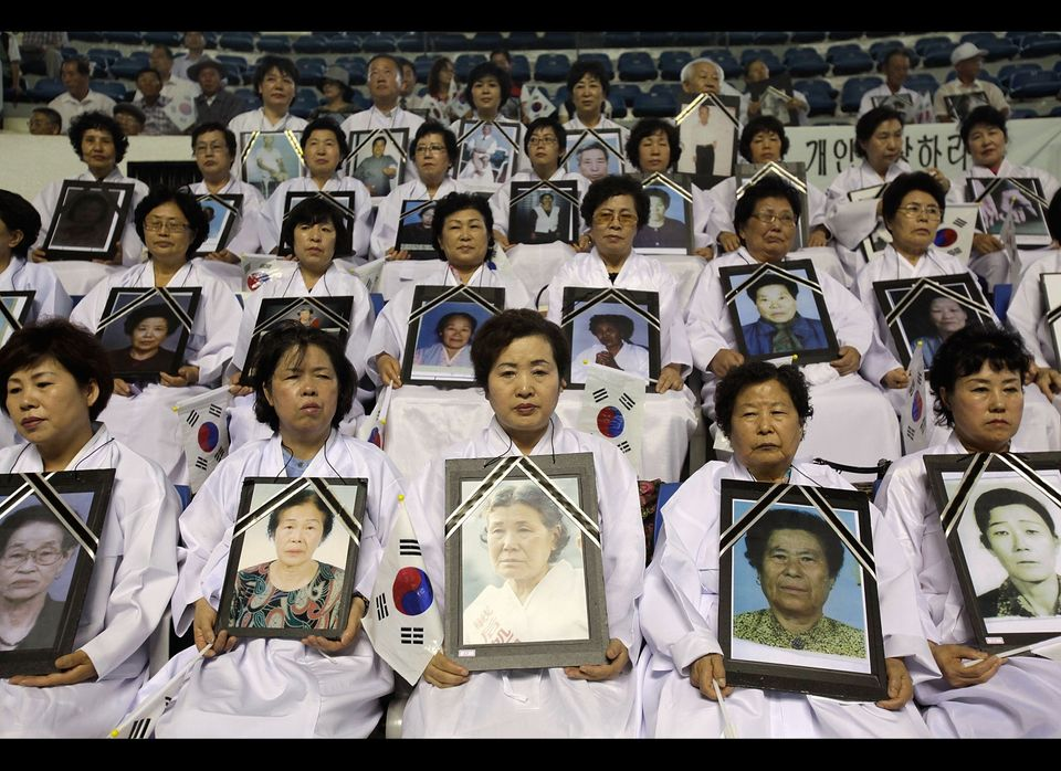 South Korean family members of victims of the World War II hold portraits of their loved ones during the 66th Independence Da