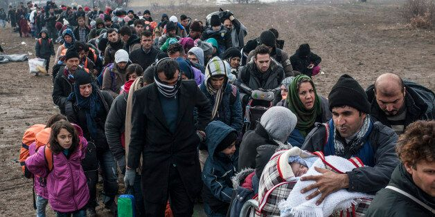 TOPSHOT - Migrants and refugees wait for security check after crossing the Macedonian border into Serbia, near the village of