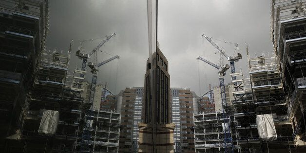 Construction cranes are reflected in the window of a neighboring building of the London Wall Place commercial property constr