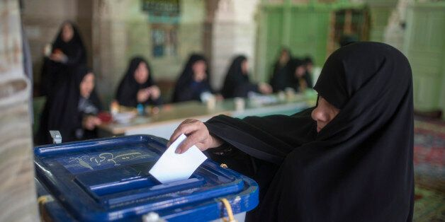 TEHRAN, IRAN - FEBRUARY 26:   An Iranian woman votes in the parliamentary and Experts Assembly elections at a polling station