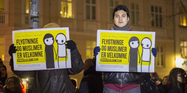 COPENHAGEN, DENMARK - JANUARY 19: The counter-demonstrators hold placards reading in 'Refugees and Muslims are welcome' durin
