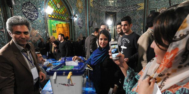 TEHRAN, IRAN - FEBRUARY 26: Iranian women take a mobile phone portrait while they vote in key elections for Parliament and th