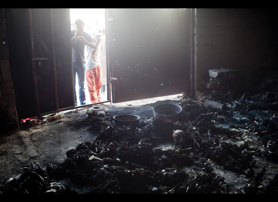 People cover their noses from the smell of burnt bodies in a warehouse on August 27, 2011 in Tripoli, Libya.  (Getty)