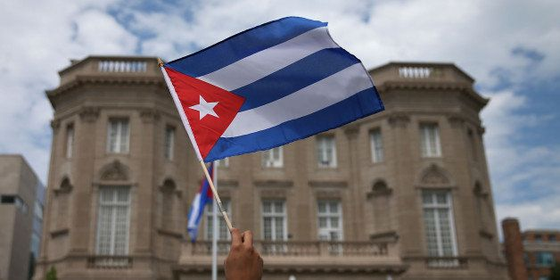 WASHINGTON, DC - JULY 20:  A supporter waves a Cuban flag in front of the country's embassy after it re-opened for the first