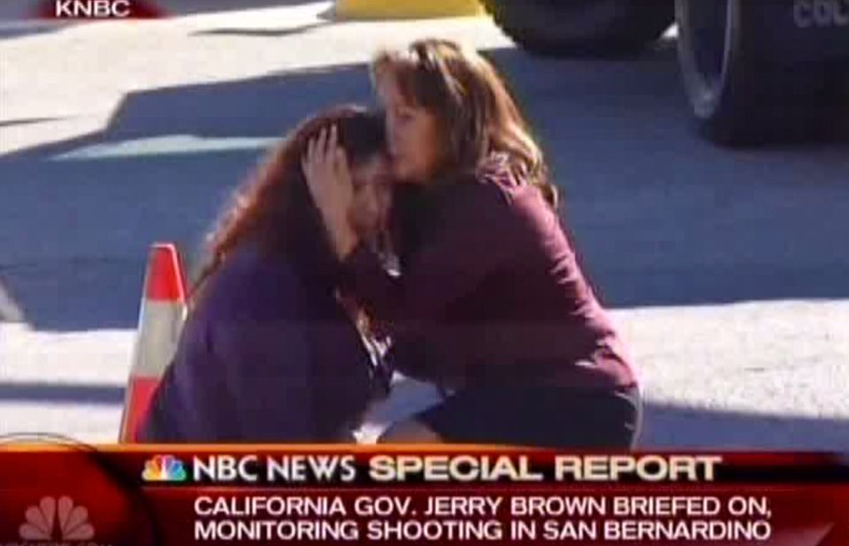 Two women comfort each other near the scene of a shooting outside a Southern California social services center in San Bernard