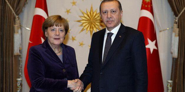 Turkish President Recep Tayyip Erdogan, right, and German Chancellor Angela Merkel shake hands before...