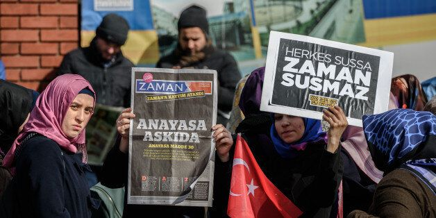 A Zaman supporter holds the latest edition of Turkish daily newspaper Zaman with the headline 'Suspended the constitution' wh