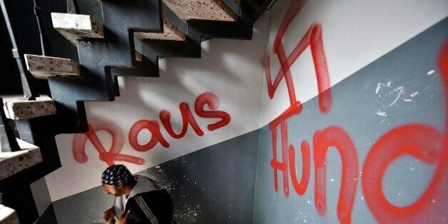 A migrant walks the stairway in a refugee housing block  in Waltrop, western Germany, painted with a swastika graffiti and a