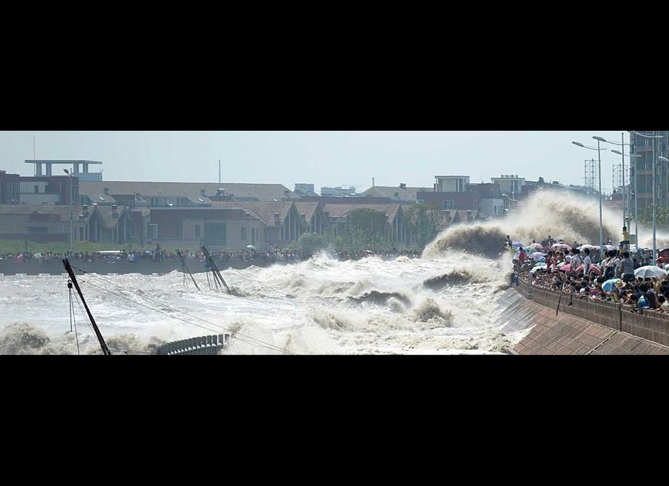 Spectators are swept by huge waves while watching tides of Qiantang River at a dike in Haining, Zhejiang Province of China. M