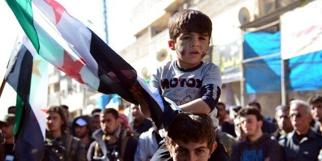 ALEPPO, SYRIA - MARCH 16: A Syrian kid holds a Syrian flag during a protest against Assad Regime at Old city of Alleppo in Sy