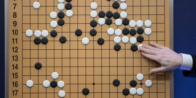 A commentator in a media room positions pieces forming a replica of a game between 'Go' player Lee Se-Dol and a Google-develo