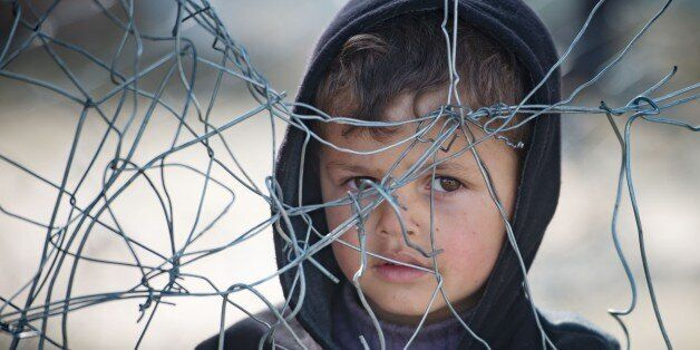 A boy stands in queue for food at a makeshift camp at the Greek-Macedonian border near the village of Idomeni on March 21, 20