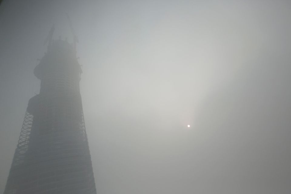 A building under construction is covered with haze in Shanghai, China, Friday, Dec. 6, 2013. Shanghai authorities ordered sch