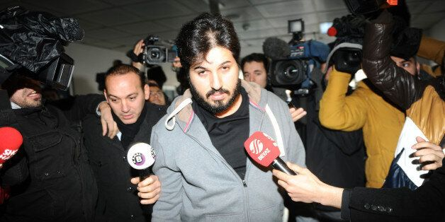 Detained Azerbaijani businessman Reza Zarrab (C) is surrounded by journalists as he arrives at a police center in Istanbul on