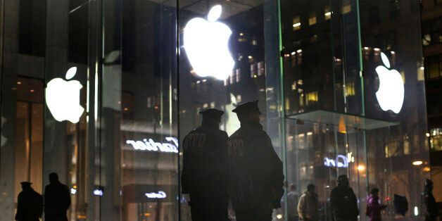 New York police officers stand outside the Apple Store on Fifth Avenue while monitoring a demonstration, Tuesday, Feb. 23, 20