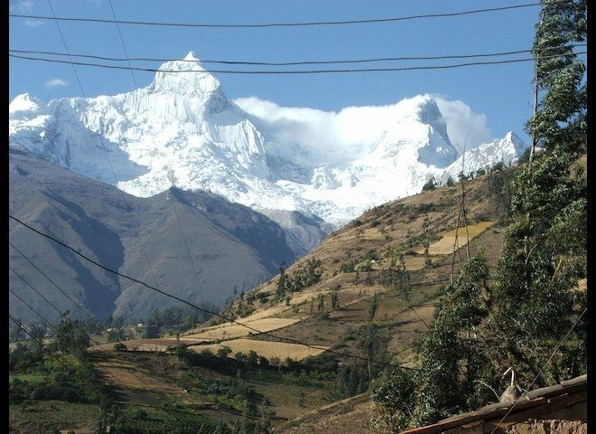 Glaciers of the Cordillera Blanca range loom above the small town of Mizac, Ancash, Peru.