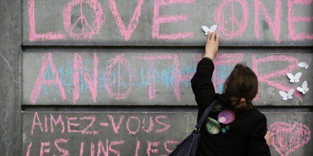 A woman sticks plastic butterfly decorations near peace messages at a makeshift memorial on the Place de la Bourse (Beursplei