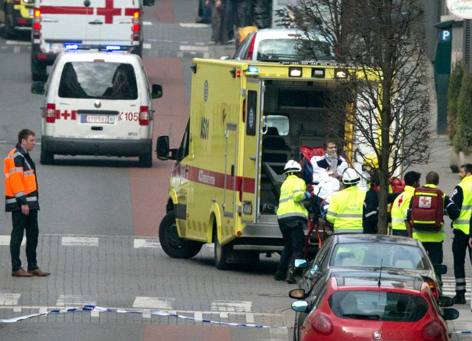 A woman is evacuated in an ambulance by emergency services after a explosion in a main metro station in Brussels on Tuesday,