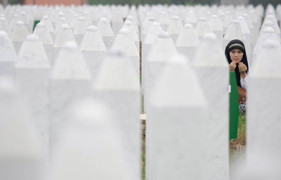 Bosnian woman Merima Nukic prays at the grave of her father during a funeral ceremony at the memorial center in Potocari, nea