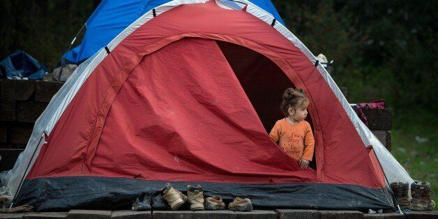 A girl stands inside a tent at a makeshift camp for migrants and refugees at the Greek-Macedonian border near the village of