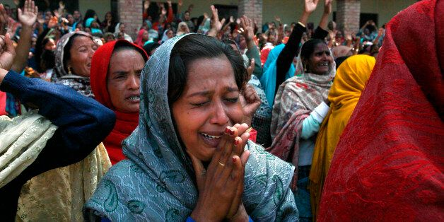 Women from the Christian community mourn for their relatives, who were killed by a suicide attack on a church, during their f