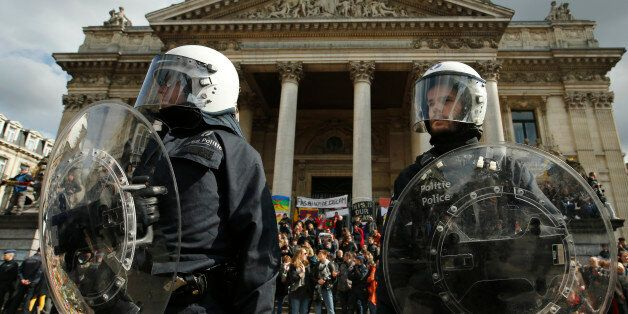 Police in riot gear protect one of the memorials to the victims of the recent Brussels attacks, as right wing demonstrators p