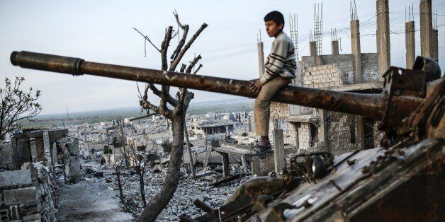 A Syrian Kurdish boy sits on a destroyed tank in the Syrian town of Kobane, also known as Ain al-Arab, on March 27, 2015. Isl