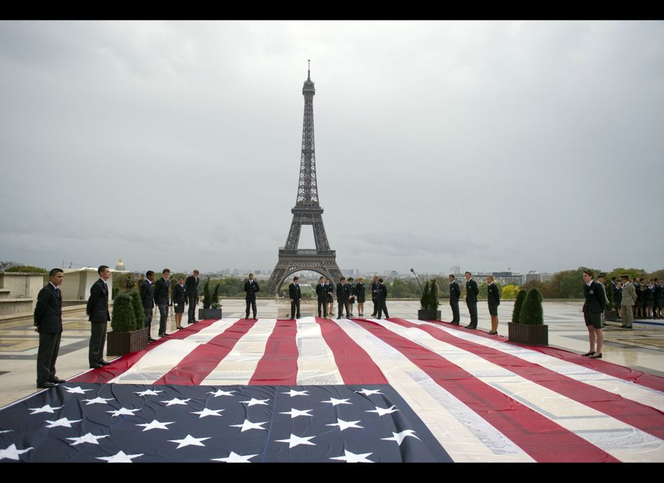 Student officers display a U.S. flag on the Trocadero square with the Eiffel tower in the background during a solemn tribute