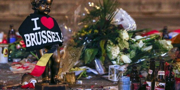 A replica of the Manneken-Pis statue, a major Brussels tourist attraction, is seen among flowers at a memorial for the victim