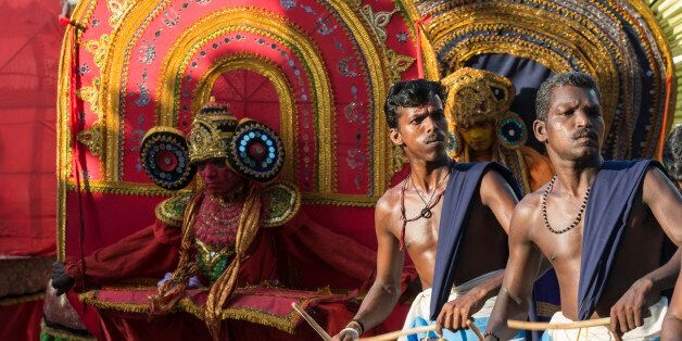 VARKALA, KERALA, INDIA - 2014/02/17: Two drummers are playing their instruments at a temple festival, theyyam dancers with ye