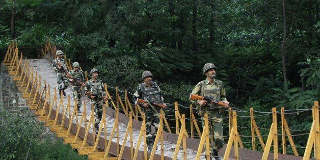 Indian Border Security Force (BSF) soldiers patrol over a footbridge near the Line of Control (LoC), a ceasefire line dividin