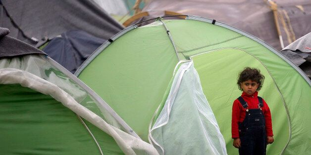 A girl stands in front of her tent in the makeshift refugee camp at the northern Greek border point of Idomeni, Greece, Satur