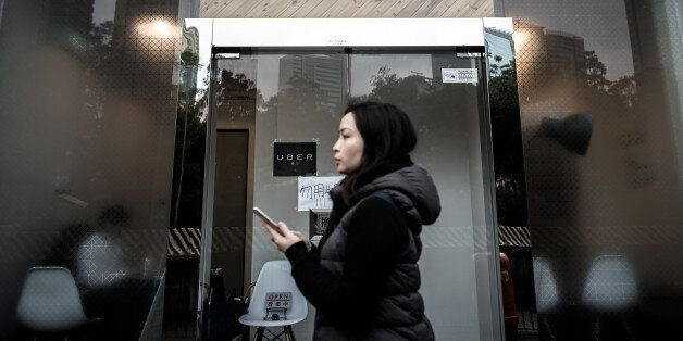 A woman walks past the Uber offices in Hong Kong on January 22, 2016. Two Hong Kong Uber drivers were fined on January 22 aft