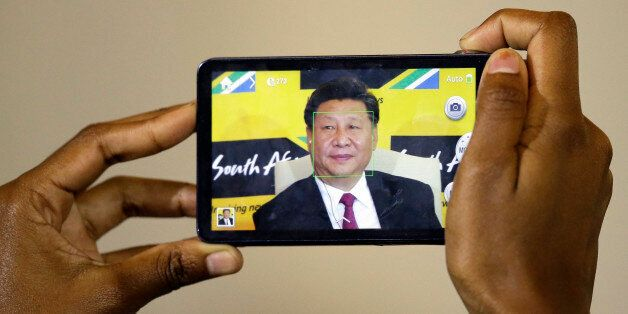 A journalist takes a photo of Chinese President Xi Jinping, using a mobile phone during a joint media conference with South A