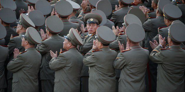 Soldiers applaud the arrival North Korean leader Kim Jong-Un during a mass military parade at Kim Il-Sung square in Pyongyang