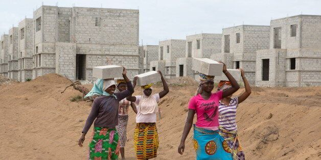 Women carry bricks at the construction site of real estate company Sipim in Grand Bassam, Ivory Coast,...