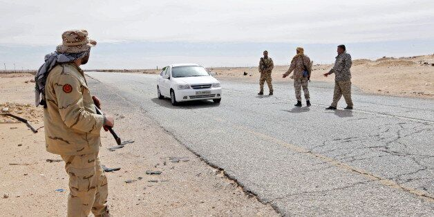 Libyan soldiers manning a military outpost, stop a car at a checkpoint in Wadi Bey, west of the city of Sirte, which is held