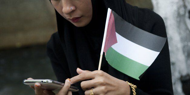 A protestor check her phone as she holds a Palestinian flag outside the Israeli embassy in Bangkok, during a demonstration ag