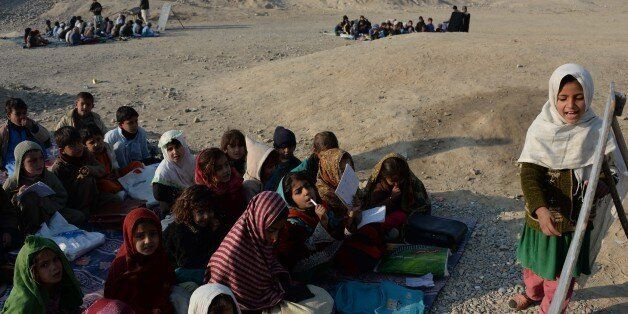 Afghan schoolchildren study at an open-air classroom in the Mohmand Dara district in eastern Nangarhar province on December 1