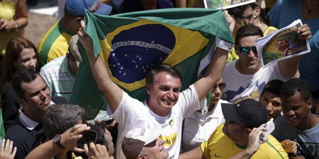 Congressman Jair Bolsonaro holds a Brazilian flag during a protest against Brazil's President Dilma Rousseff, part of nationw